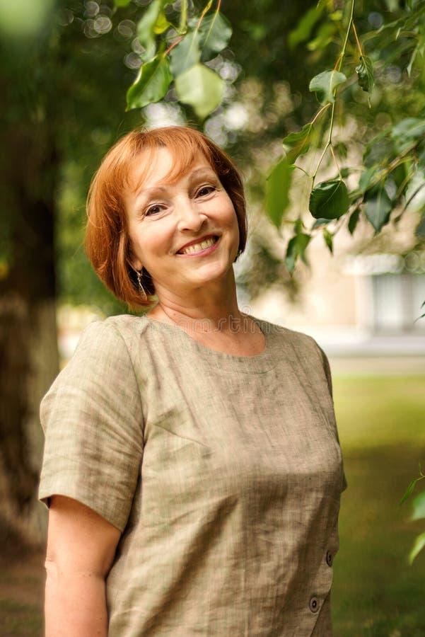 一名年长可爱的微笑的妇女的画象一件亚麻制礼服的在一棵绿色树的叶子 库存图片
