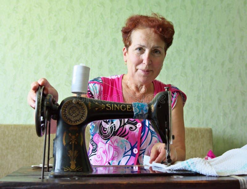 一名年长妇女在一台老缝纫机缝合 图库摄影