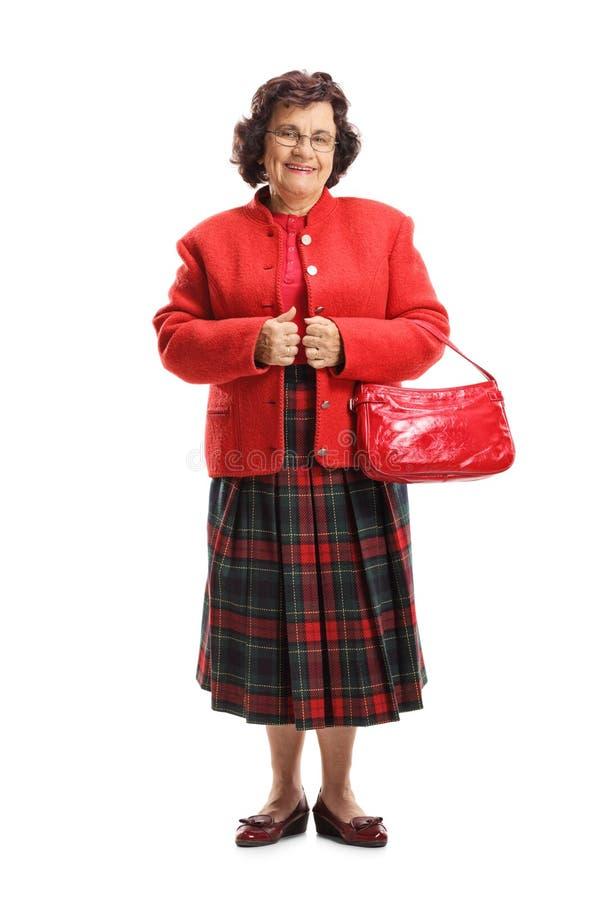 一名年长妇女的全长画象有在白色背景隔绝的一个红色钱包的 免版税库存照片