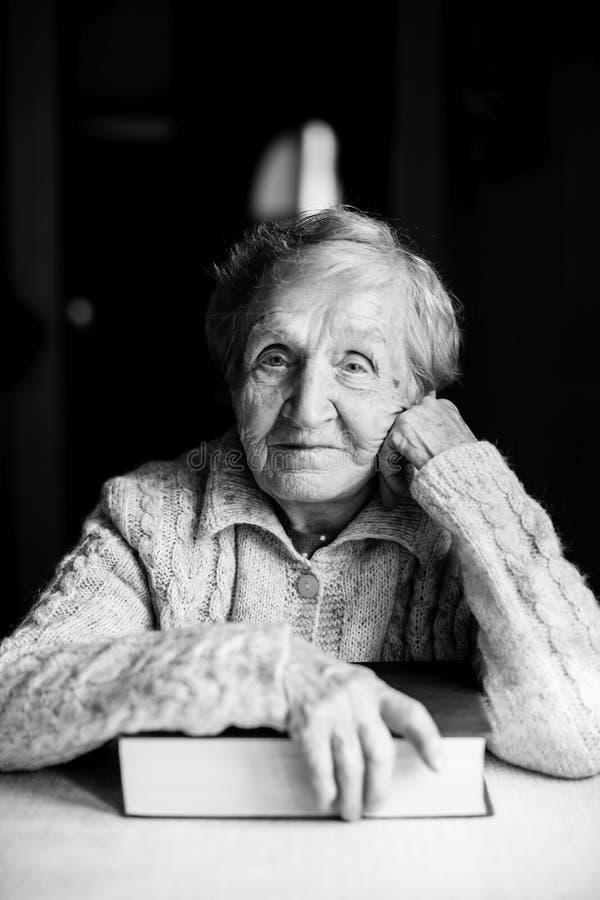 一名年长妇女的画象有书的 图库摄影