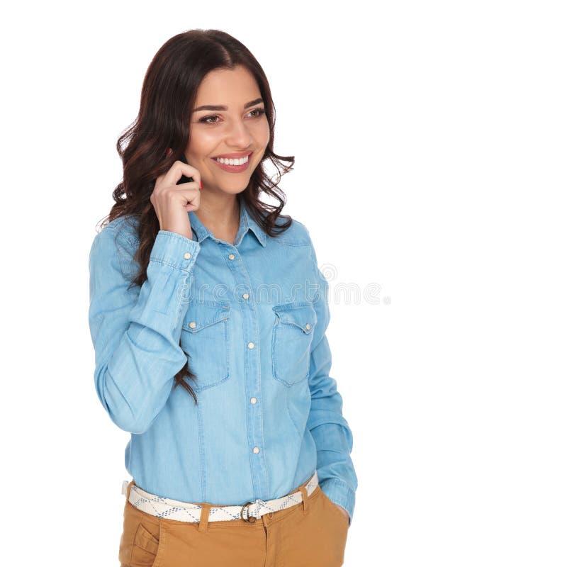 一名微笑的偶然妇女的侧视图谈话在机动性 免版税库存图片