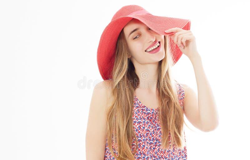 一名微笑的可爱的妇女的画象摆在夏天的礼服和的帽子的,当站立和看照相机被隔绝在白色时 库存图片