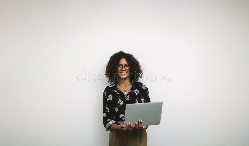 一名微笑的女实业家的画象在拿着膝上型计算机的办公室 图库摄影