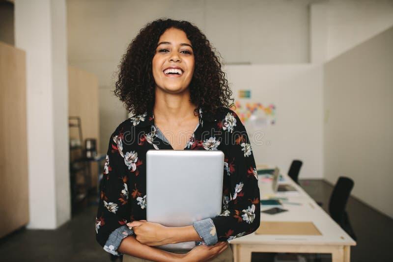 一名微笑的女实业家的画象在拿着膝上型计算机的办公室 库存照片