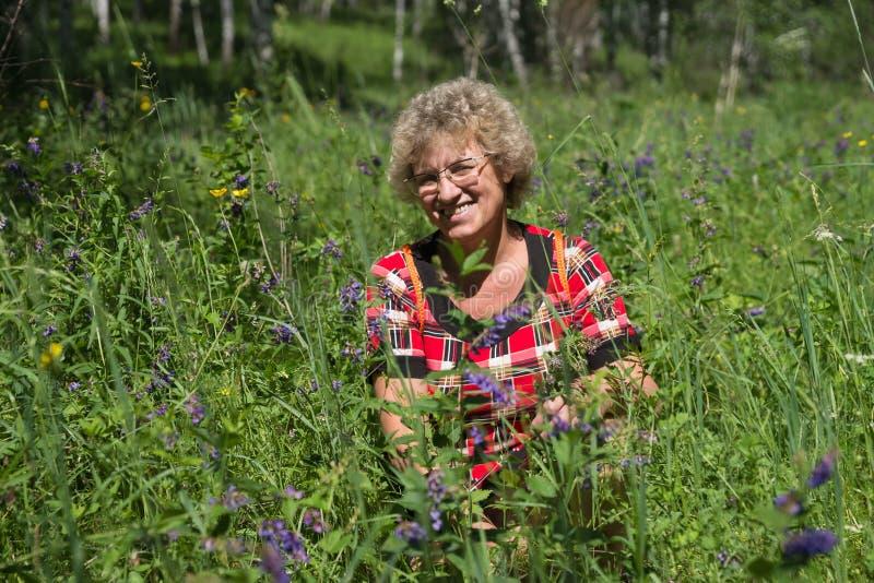 一名微笑的妇女在一个开花的草甸中间坐 免版税图库摄影