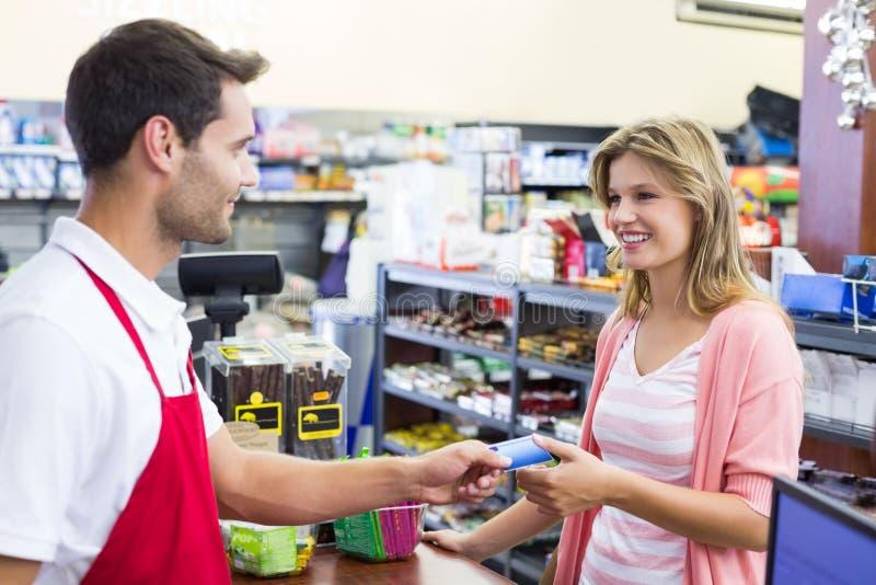 一名微笑的妇女的侧视图支付与信用卡的收款机的 免版税库存照片