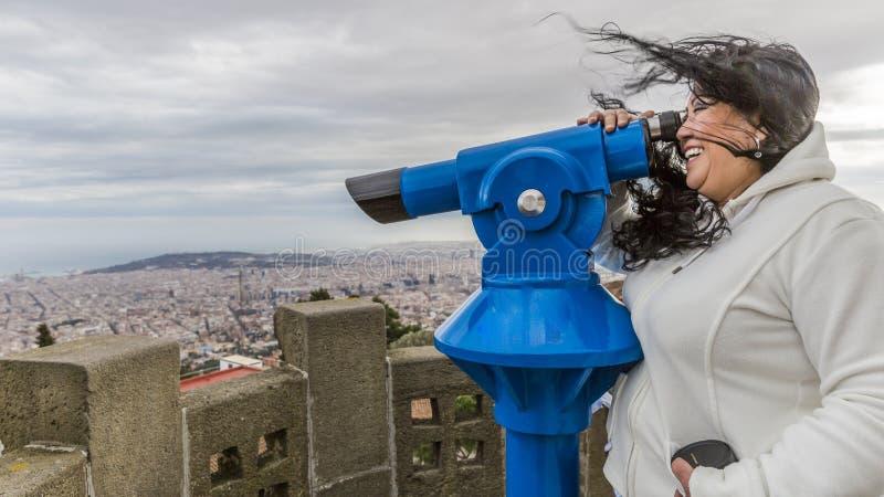 一名微笑的妇女的滑稽的图象有风弄乱的她的头发的观察通过望远镜 免版税图库摄影