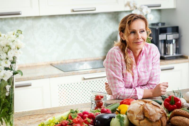 一名微笑的妇女的纵向在厨房里 库存图片