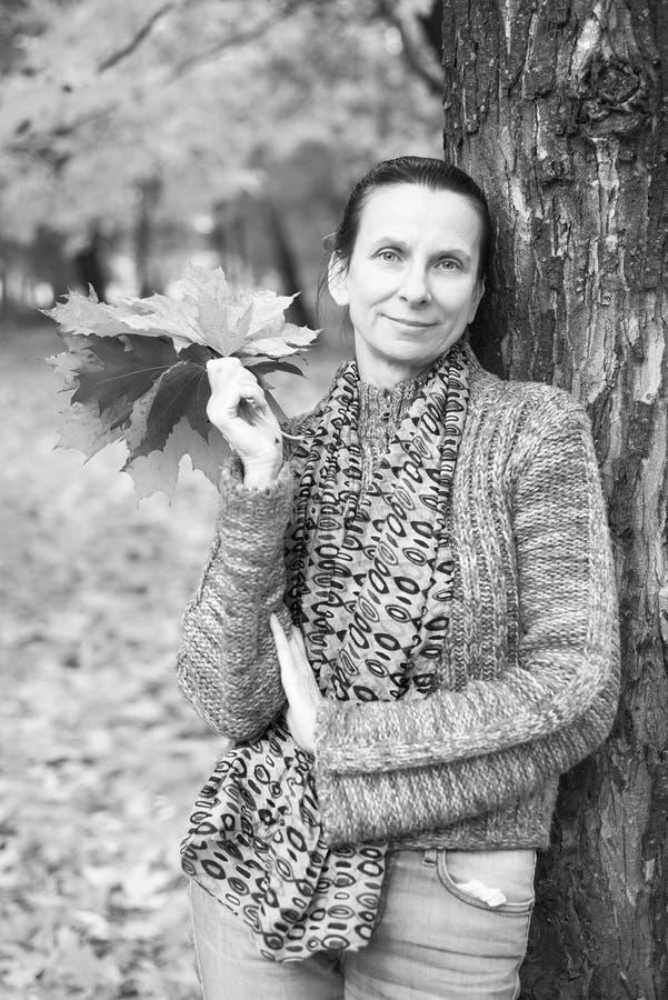 一名微笑的成人白种人妇女的黑白画象在秋天采摘黄色枫叶 免版税库存照片