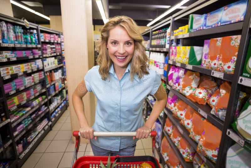 一名微笑的白肤金发的妇女的画象走道的有她的台车的 图库摄影