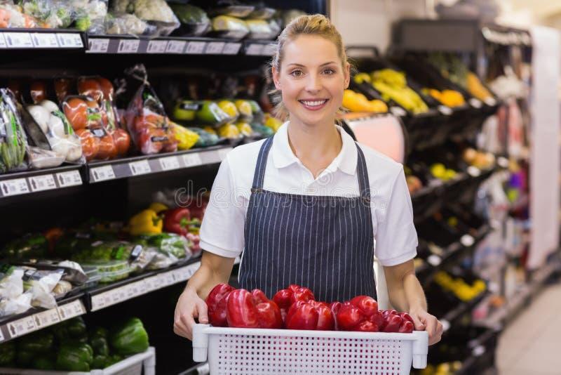 一名微笑的白肤金发的工作者的画象拿着菜 免版税库存图片