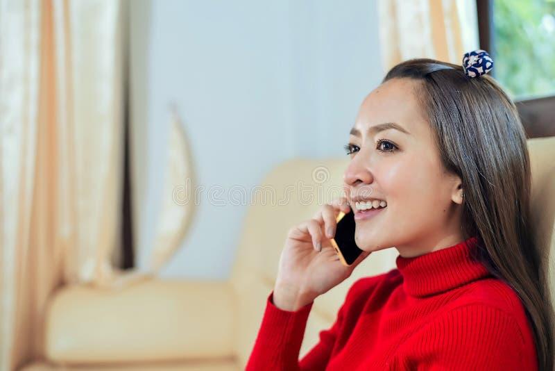 一名微笑的美丽的妇女的画象谈话在长沙发的电话在家 免版税库存图片