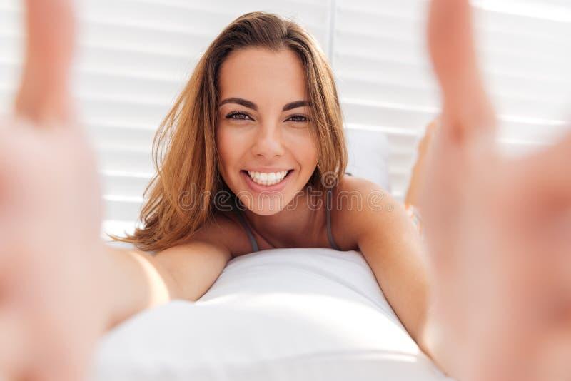 一名微笑的逗人喜爱的妇女的画象做selfie的比基尼泳装的 库存图片