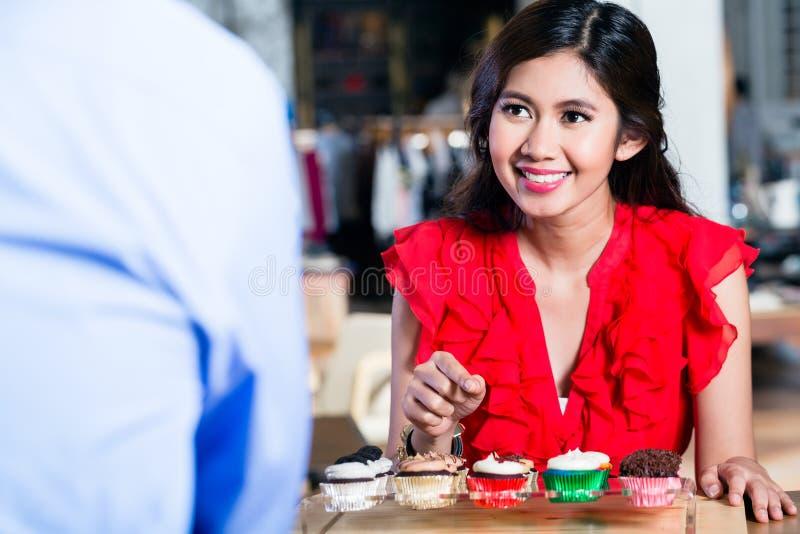 一名快乐的亚裔在一个凉快的咖啡馆的妇女预定的杯形蛋糕的画象 免版税库存照片