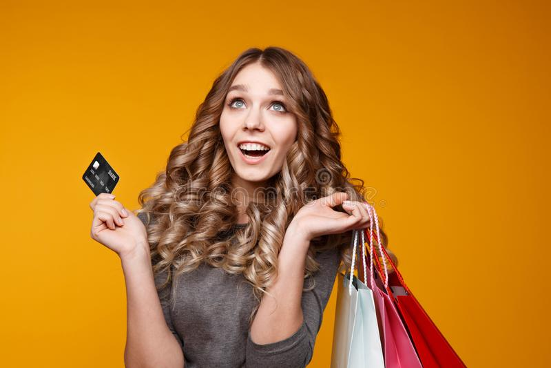 一名快乐的年轻深色的妇女的图片拿着信用卡的白色夏天礼服的摆在与购物带来和 库存照片