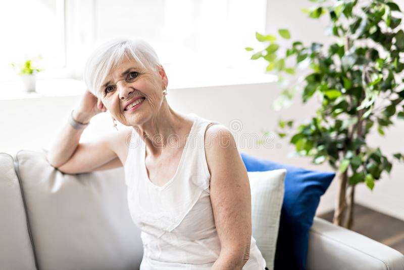 一名快乐的资深妇女的画象坐沙发在客厅 免版税库存图片