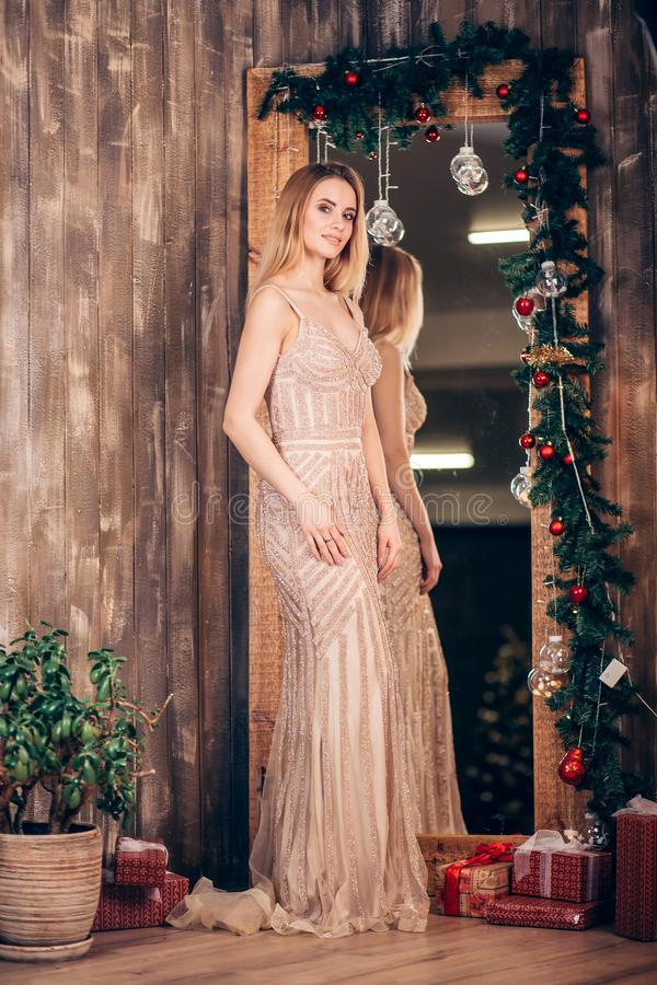 一名性感的典雅的白肤金发的妇女的全长画象一件长的金黄礼服的在用圣诞节分支装饰的镜子附近和 免版税库存照片