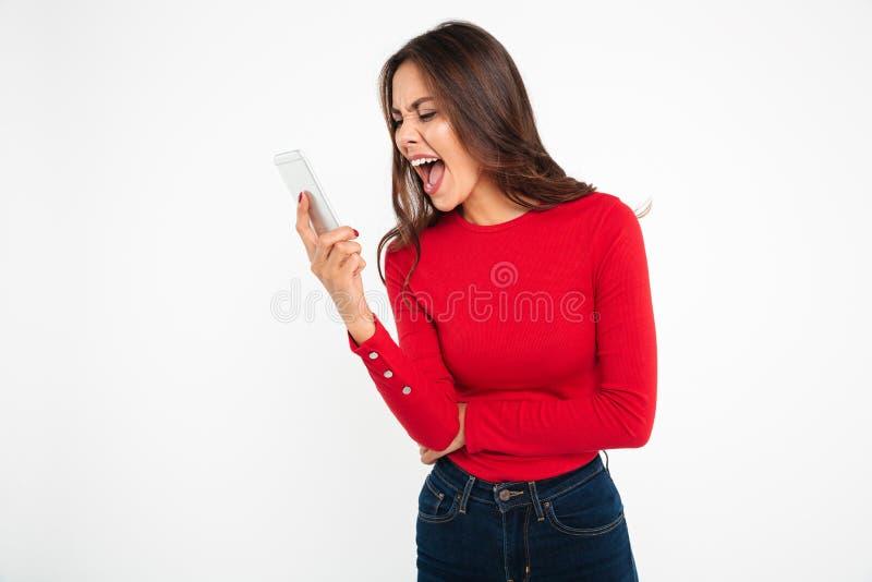 一名恼怒的亚裔妇女的画象叫喊对手机 库存图片