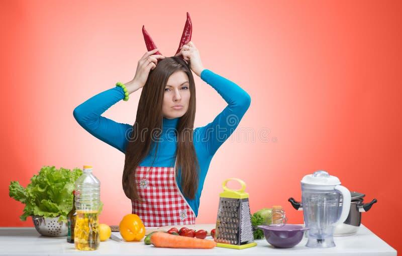 一名恼怒的妇女的滑稽的画象在厨房里 库存图片