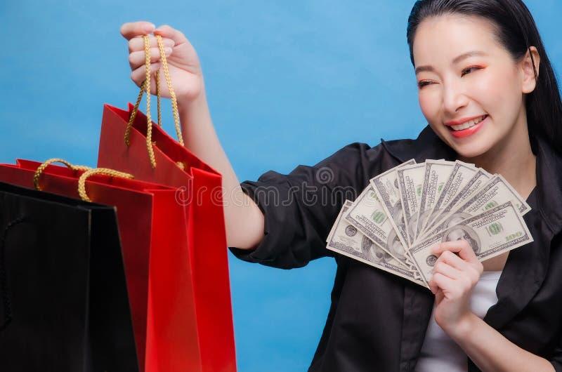 一名愉快的中国妇女的画象拿着红色购物带来和金钱的黑衬衣的隔绝在蓝色背景 免版税图库摄影
