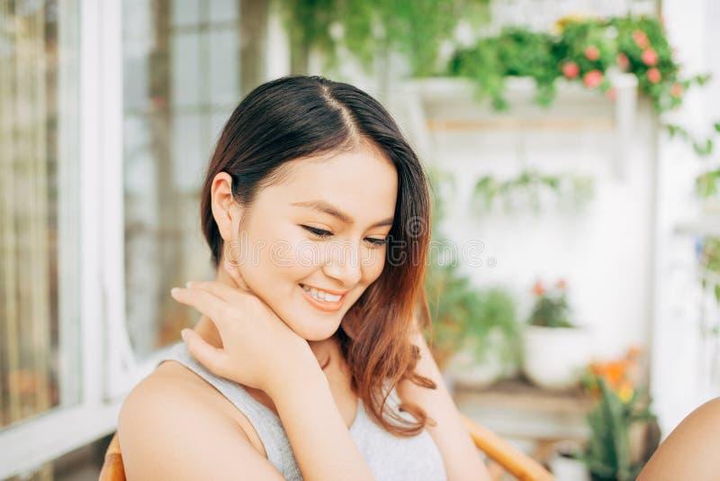 一名愉快的亚裔妇女坐一把椅子在阳台上早晨 图库摄影