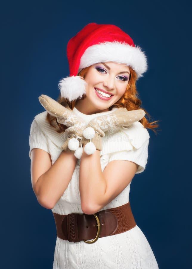 一名愉快的妇女在冬天在蓝色bg穿衣 库存照片