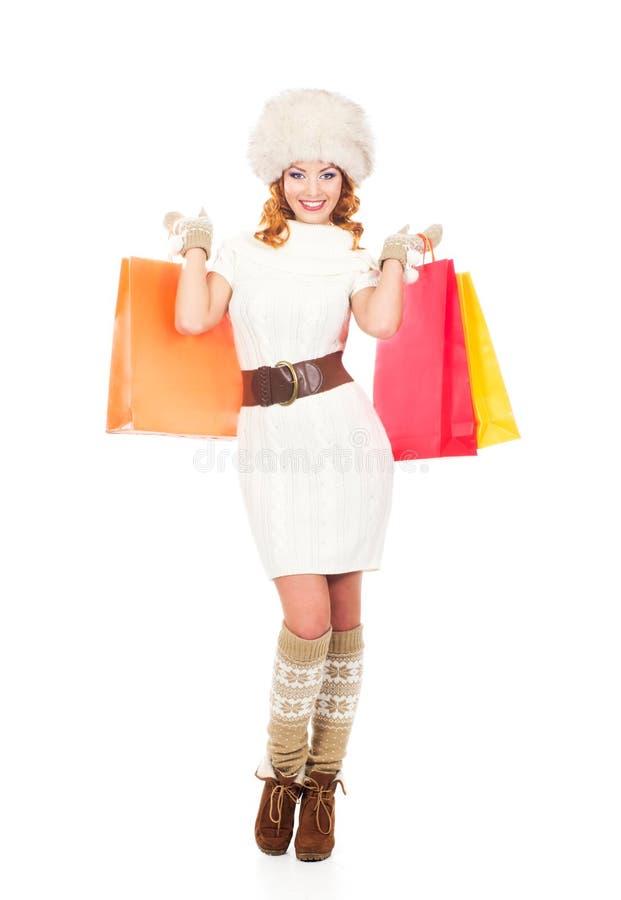 一名愉快的妇女在冬天穿衣与购物袋 免版税图库摄影
