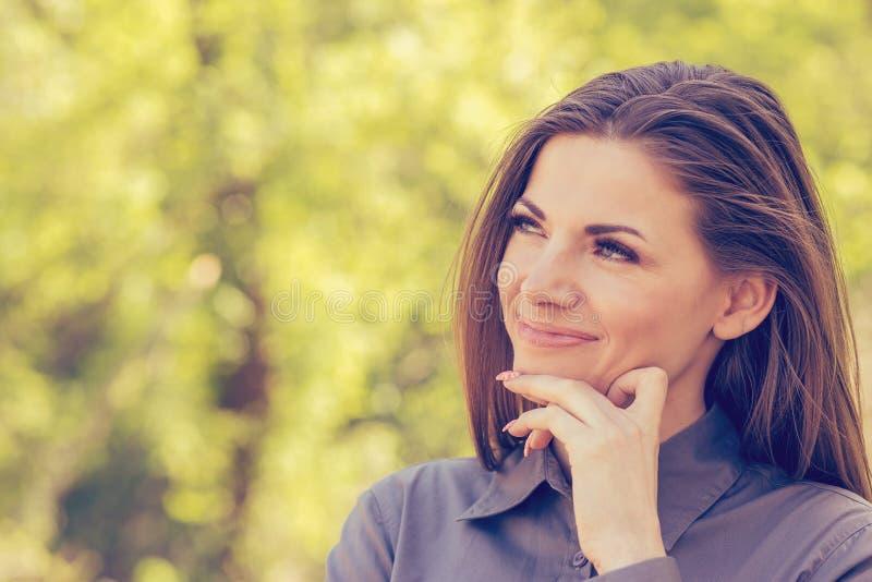 一名愉快的妇女的画象在晴朗的秋天下午的公园 快乐的美丽的女孩灰色衬衣的和户外美好的秋天的 图库摄影