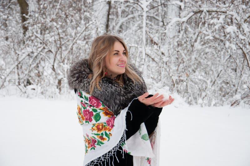 一名愉快的妇女通过冬天森林,与雪球的戏剧走,笑并且享有生活 图库摄影