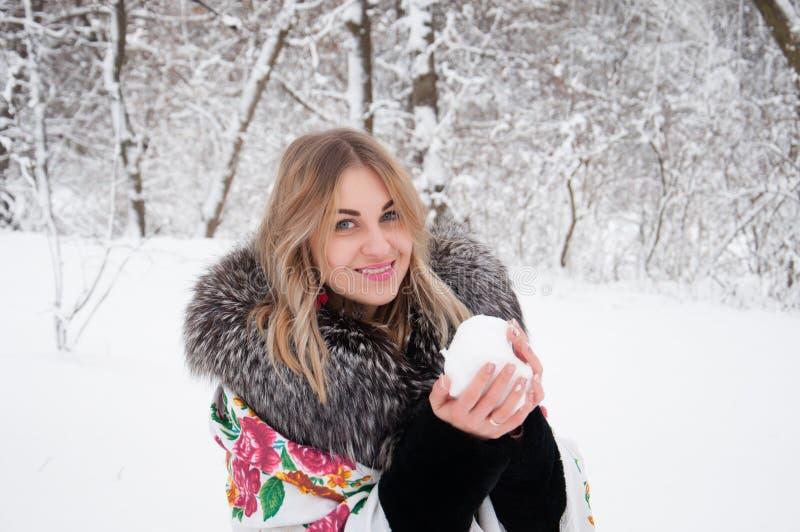 一名愉快的妇女通过冬天森林,与雪球的戏剧走,笑并且享有生活 库存照片