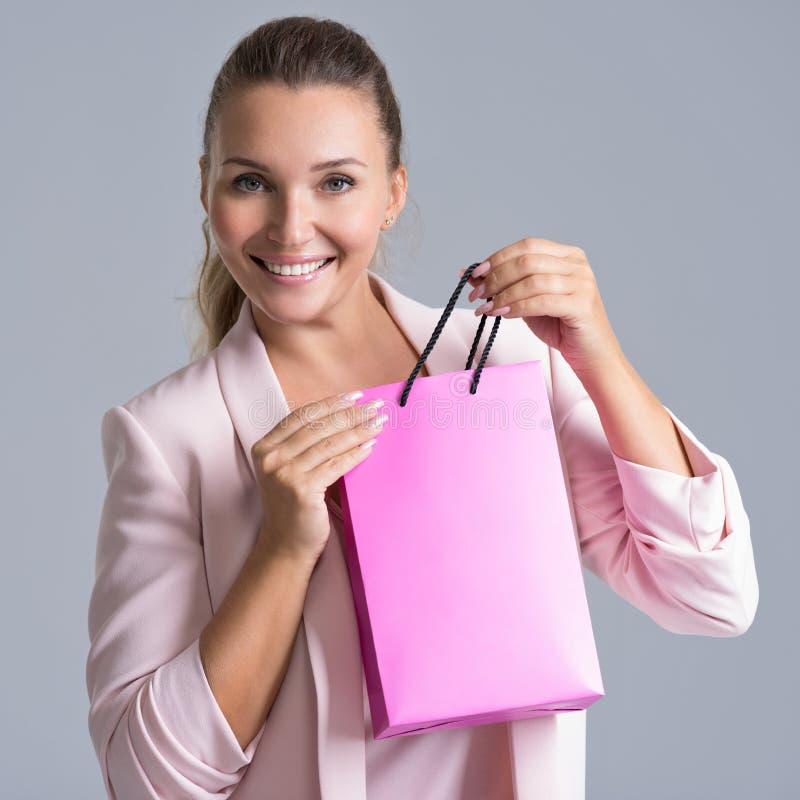 一名愉快的微笑的妇女的画象有桃红色购物袋的 免版税库存照片