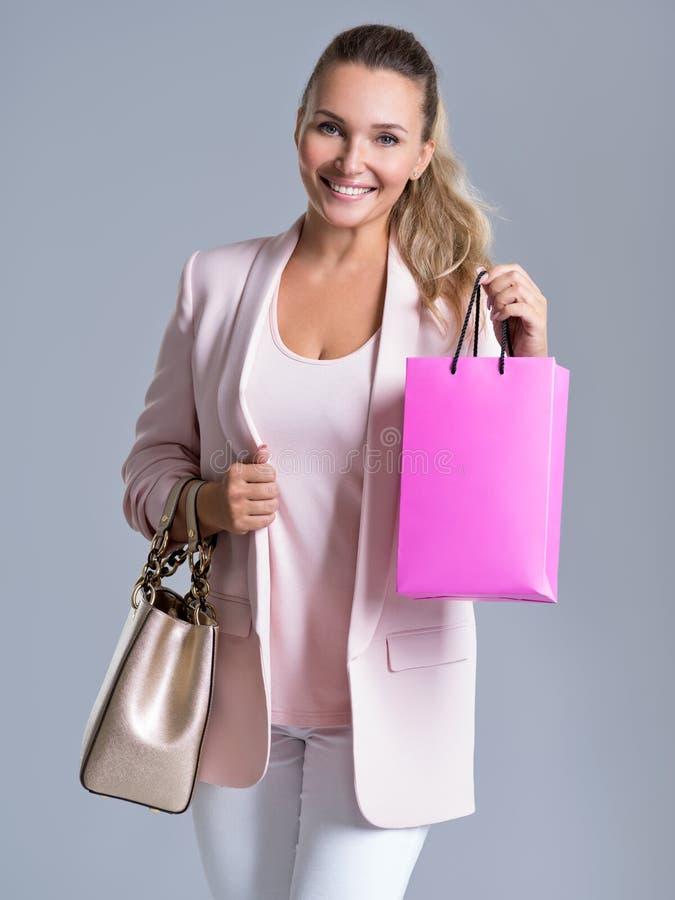一名愉快的微笑的妇女的画象有桃红色购物袋的 免版税库存图片