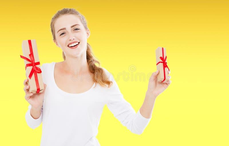 一名愉快的微笑的妇女的画象,拿着在黄色背景,假日背景的白色衬衫的女孩当前箱子 免版税库存图片