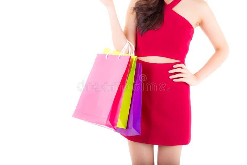 一名愉快的激动的亚裔妇女的特写镜头画象站立和拿着五颜六色的购物袋的红色礼服的 库存照片
