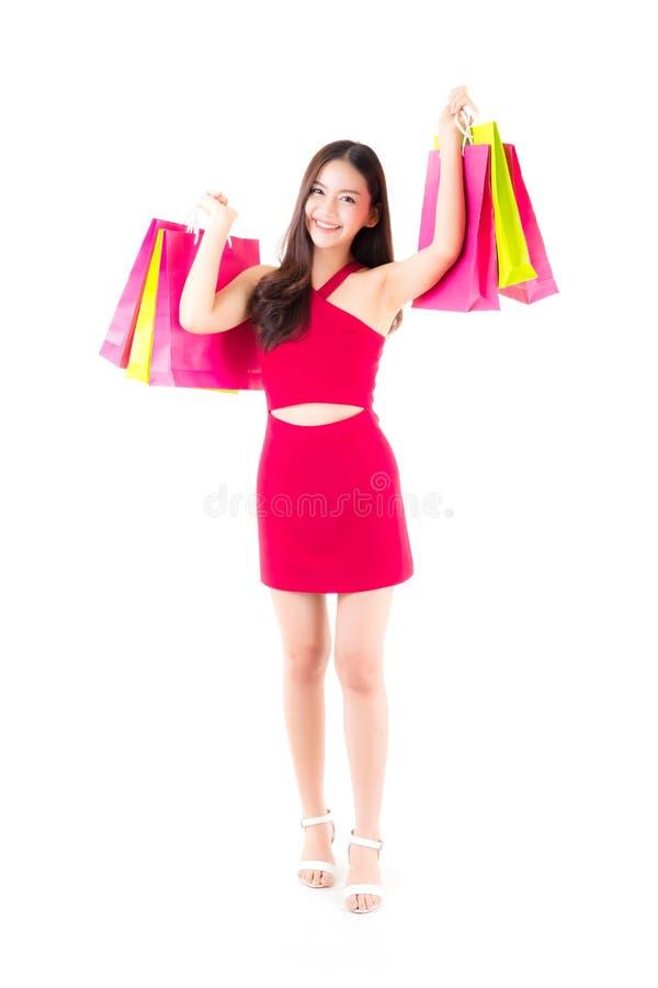 一名愉快的激动的亚裔妇女的画象站立和拿着颜色纸袋的红色礼服的 库存照片