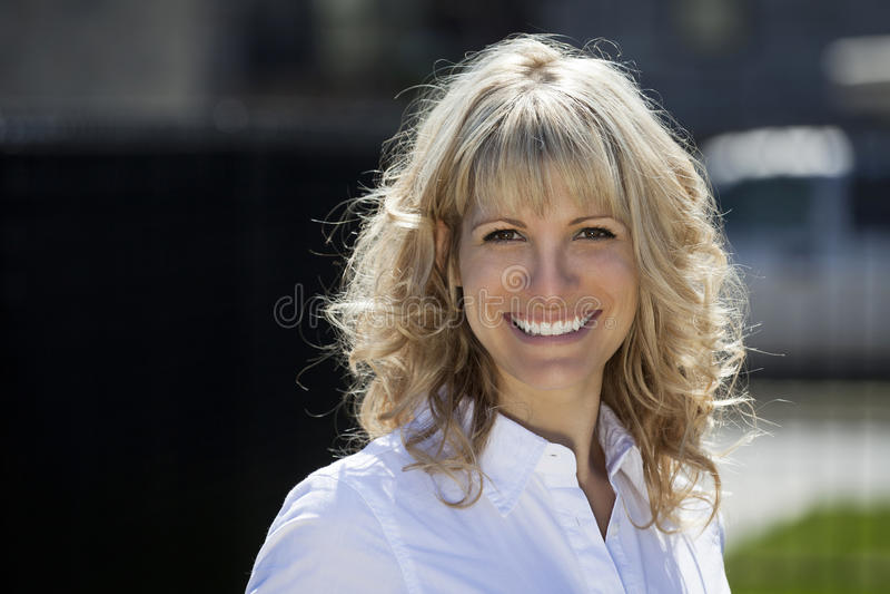 一名愉快的白肤金发的妇女的画象外面 免版税库存照片
