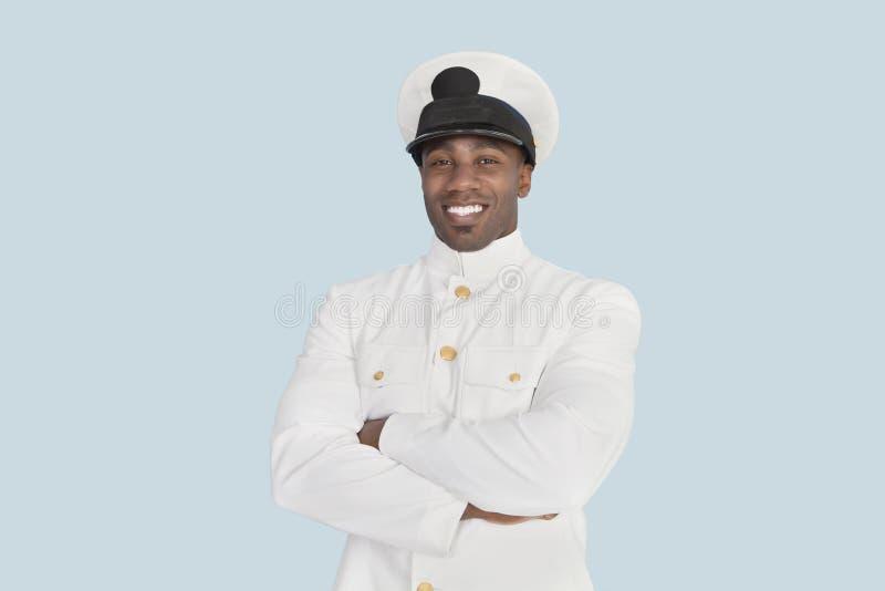一名愉快的年轻美国海军官员的画象有胳膊的横渡了在浅兰的背景 免版税图库摄影