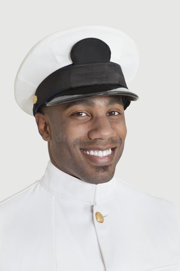 一名愉快的年轻非裔美国人的美国海军官员的画象在灰色背景的 免版税库存照片