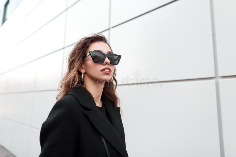 一名时髦的年轻行家妇女的画象时髦玻璃的在有性感的嘴唇的一黑色大衣有豪华金耳环的 图库摄影