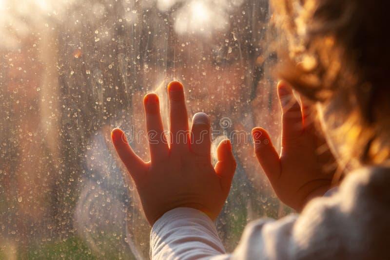 一名望窗的儿童因冠状病毒感染被迫留在家中 免版税库存照片