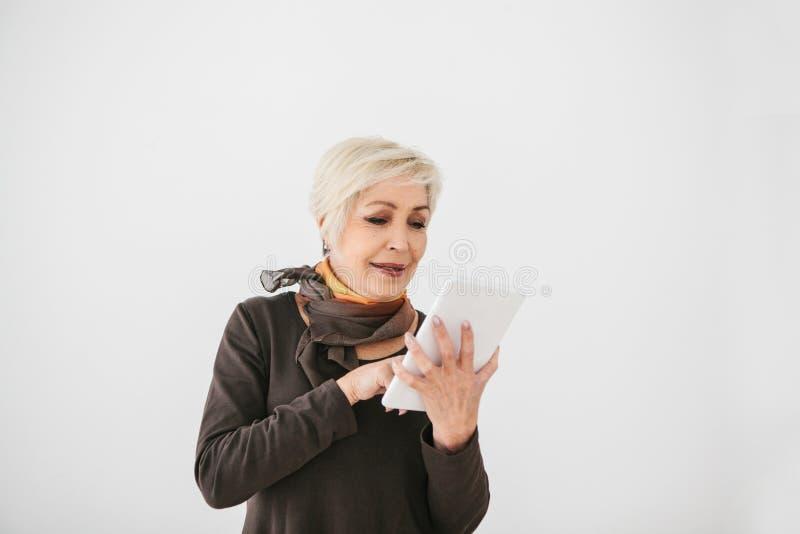 一名正面现代年长妇女在她的手上拿着一种片剂并且使用它 更旧的一代和现代技术 免版税库存图片