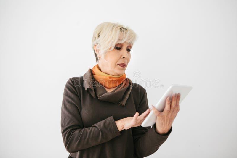 一名正面现代年长妇女在她的手上拿着一种片剂并且使用它 更旧的一代和现代技术 库存照片
