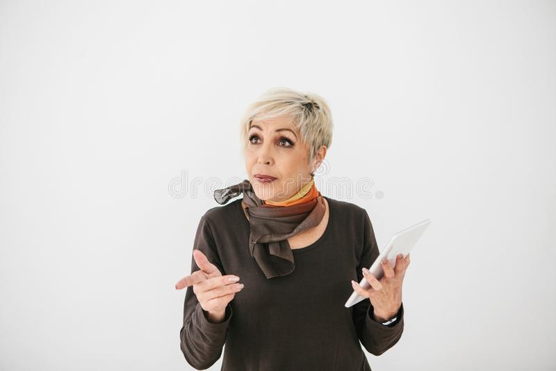 一名正面现代年长妇女在她的手上拿着一种片剂并且使用它 更旧的一代和现代技术 免版税库存照片