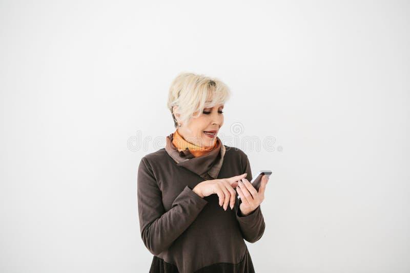 一名正面现代年长妇女拿着一个手机和使用它 更旧的一代和现代技术 图库摄影