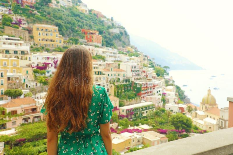 一名浪漫甜妇女的美好的背面图看从大阳台的绿色礼服的波西塔诺村庄,阿马尔菲海岸,意大利 免版税库存图片
