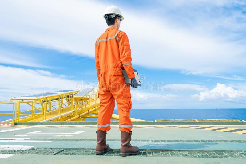 一名海上石油钻井平台工作人员佩戴个人防护设备,站在海上井口远程平台上 库存图片
