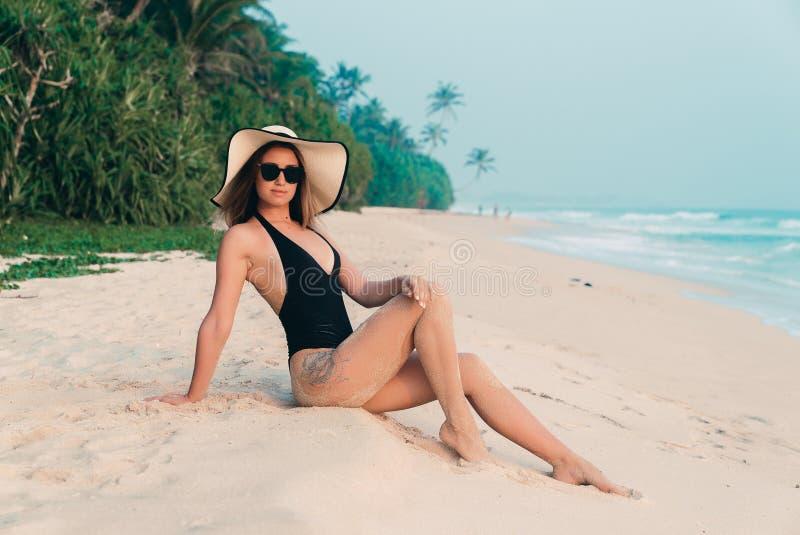一名甜嫩欧洲妇女坐白色沙子,享受在一个空的海滩的寂寞,戴有宽的一个时兴的帽子 免版税库存照片