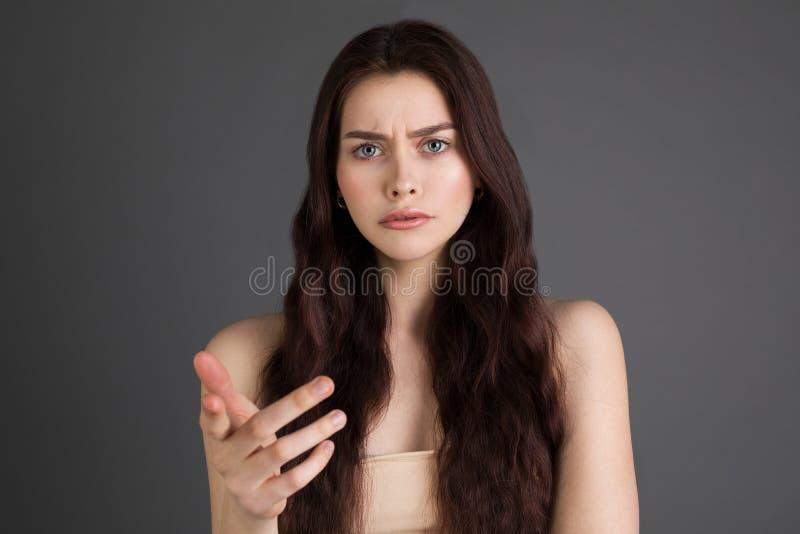 一名生气,严肃,恼怒的妇女的画象有长的深色的头发的 免版税图库摄影