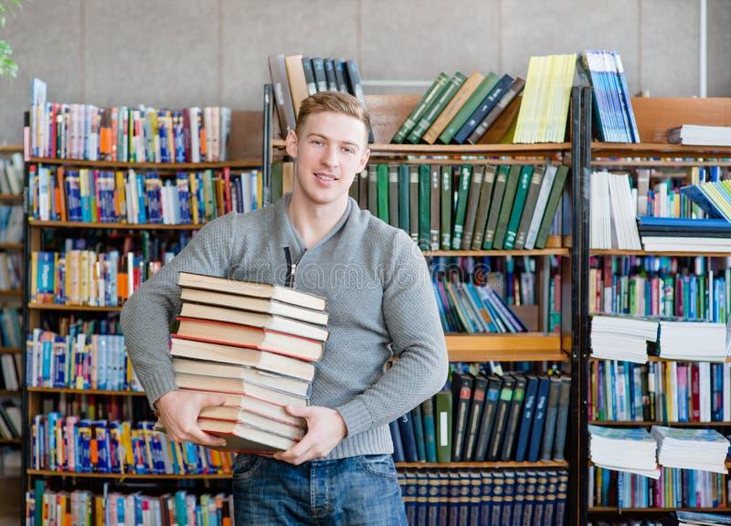 一名男学生的画象有堆的在大学图书馆里预定 免版税库存图片
