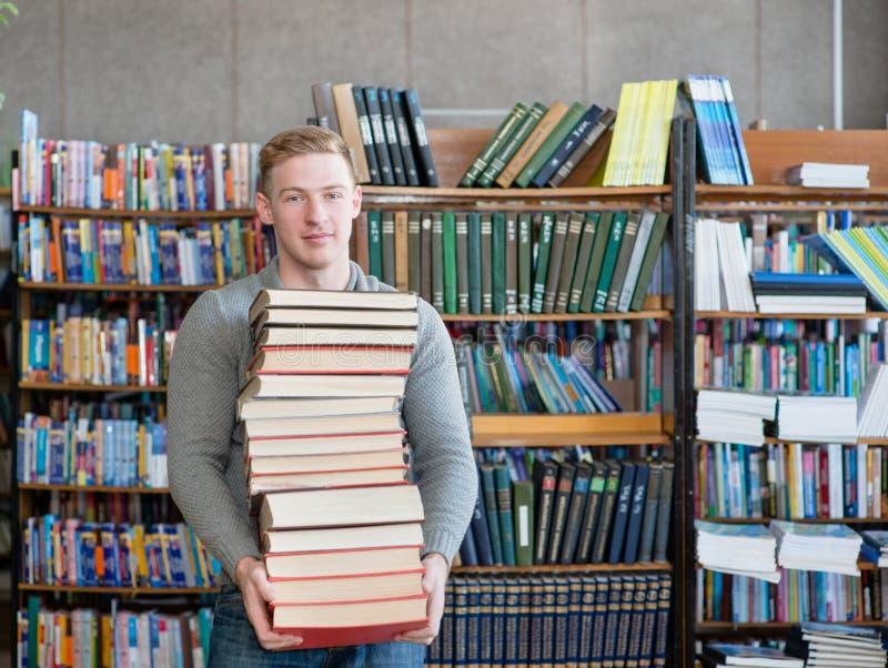 一名男学生的画象有堆的在大学图书馆里预定 免版税库存照片